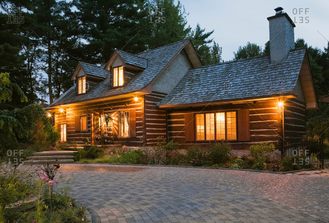Reconstructed 1976 cottage style log home facade in the evening, Quebec, Canada