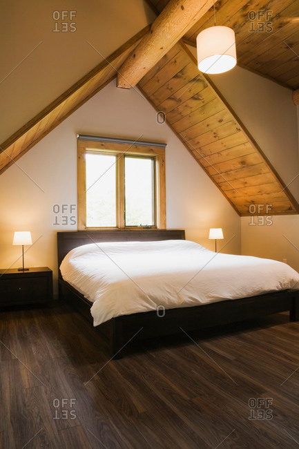 Vaulted ceiling and double bed below window in modern bedroom