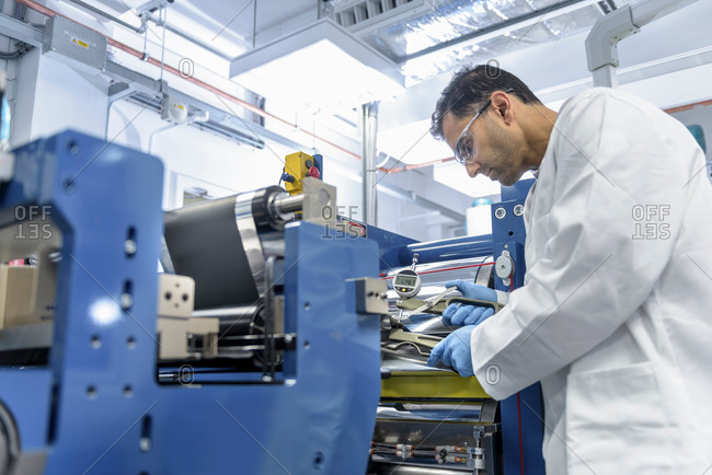Scientist manufacturing lithium ion batteries in battery research facility