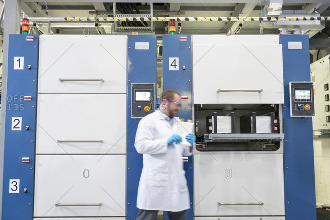 Scientist walking by lithium ion pouch cell manufacture machine in battery research facility