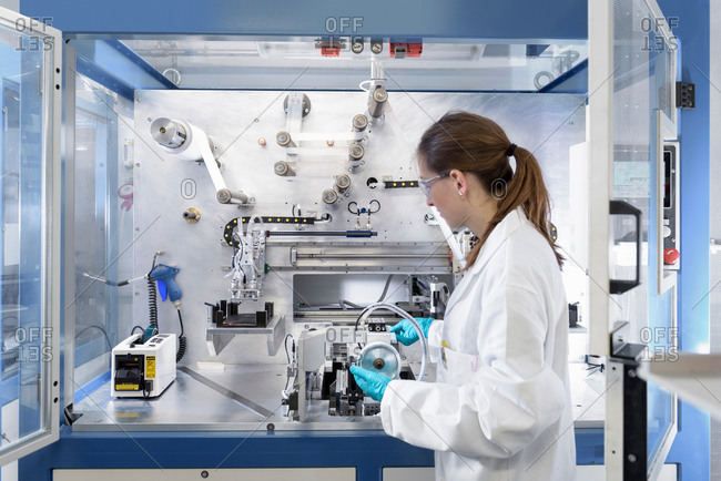 Female scientist making lithium ion battery samples in battery research facility