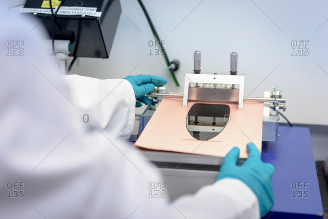 Scientist making lithium ion battery samples in battery research facility, close up