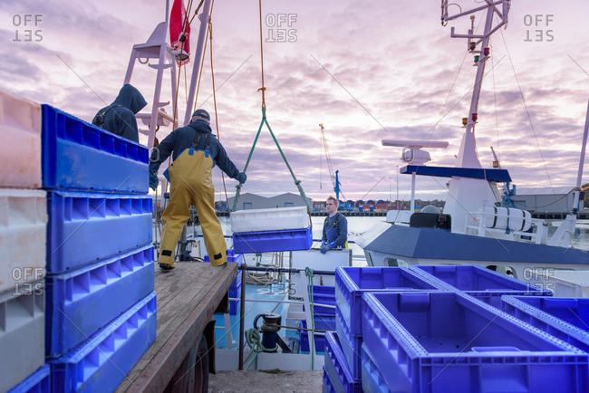 Fishermen unloading fish from trawler in the evening