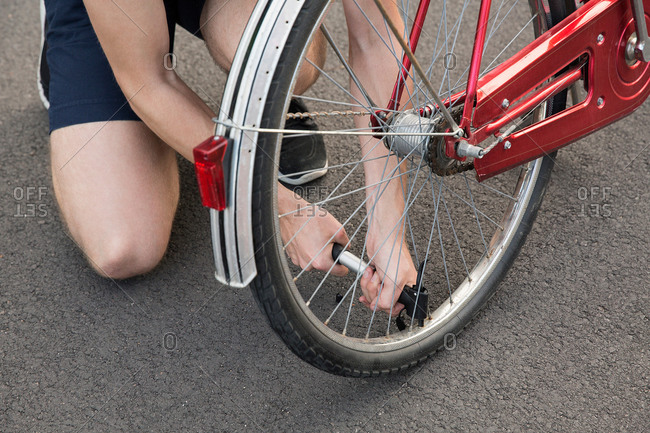 View of young man kneeling inflating bicycle tire
