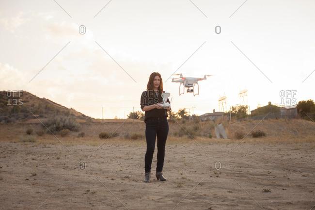 Female commercial operator on scrubland flying drone, Santa Clarita, California, USA