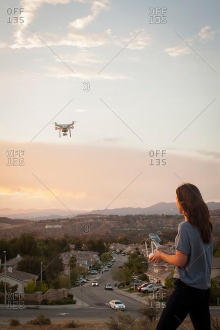 Female commercial operator flying drone above housing development, Santa Clarita, California, USA