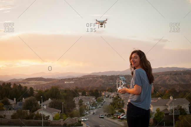 Female commercial operator flying drone above housing development, looking over shoulder