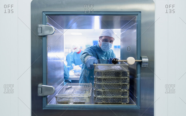 Worker putting surgical instruments into air lock in clean room of surgical instruments factory