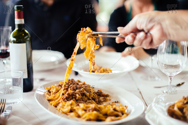 Woman's hand serving tagliatelle with ragu sauce at table