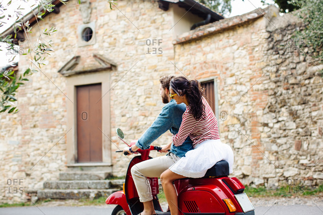Young couple riding moped in village, Florence, Italy
