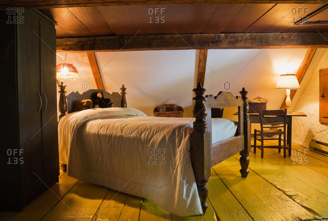 Bed in room with wood beamed vaulted ceiling