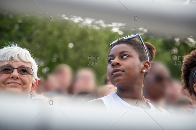 Senior woman and family watching graduation ceremony