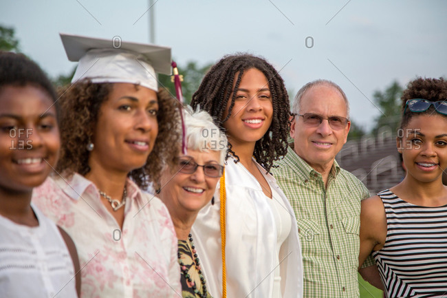 Teenage girl with family at graduation ceremony