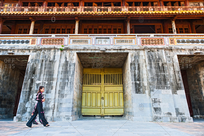 Woman walking, in traditional Ao Dai dress at the old imperial city in Hue, Vietnam