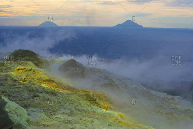 Sulfur and fumarole smoke at Gran Cratere and view of islands, Vulcano Island, Aeolian Islands, Sicily, Italy