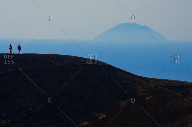 Two silhouetted tourists walking crater rim, Vulcano Island, Aeolian Islands, Sicily, Italy
