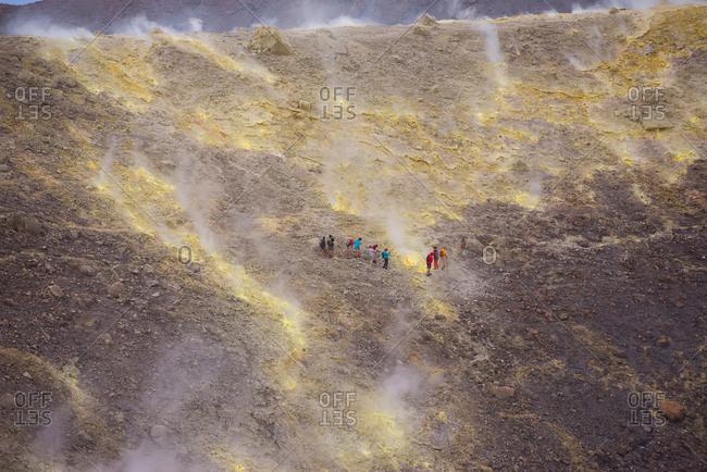 Group of tourists walking through fumarole smoke at Gran Cratere, Vulcano Island, Aeolian Islands, Sicily, Italy