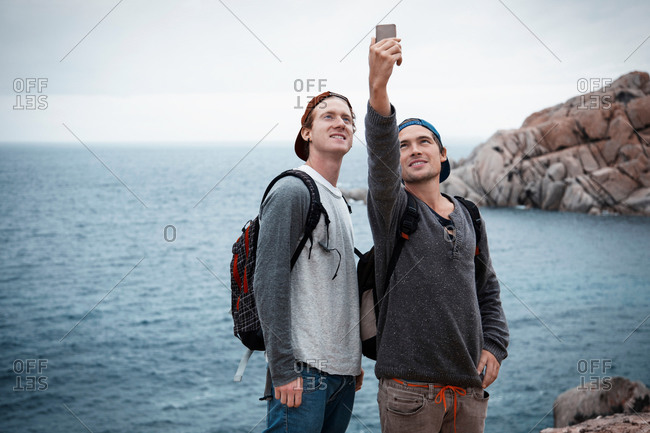 Young men in front of ocean using smartphone to take selfie smiling, Costa Smeralda, Sardinia, Italy