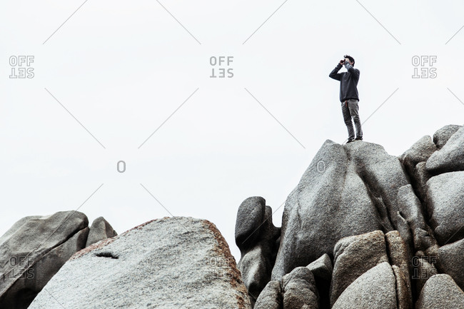 Low angle view of young man standing on rocks, pretending to use binoculars, Costa Smeralda, Sardinia, Italy