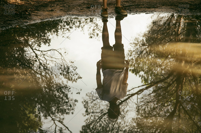 Full length reflection of young man in puddle, Costa Smeralda, Sardinia, Italy