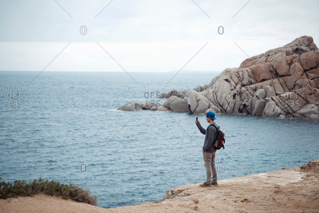 Young man standing on cliff using smartphone to photograph ocean, Costa Smeralda, Sardinia, Italy