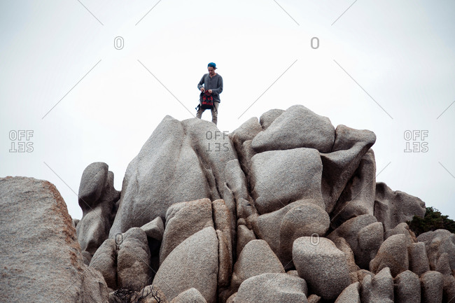 Low angle view of young man standing on rocks holding backpack looking down, Costa Smeralda, Sardinia, Italy