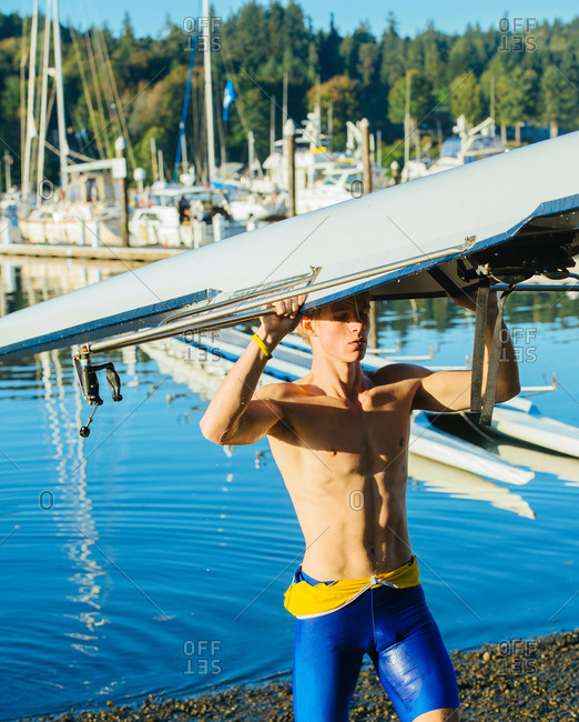Teenage boy holding sculling boat above head