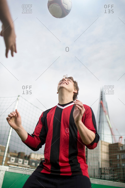 Young man practicing soccer skills on urban soccer field