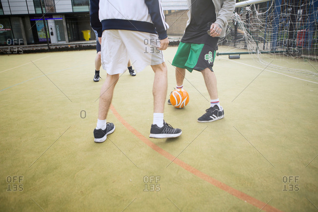 Group of adults playing soccer on urban soccer field, low section