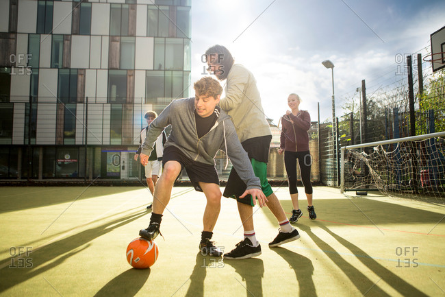 Group of adults playing soccer on urban soccer field