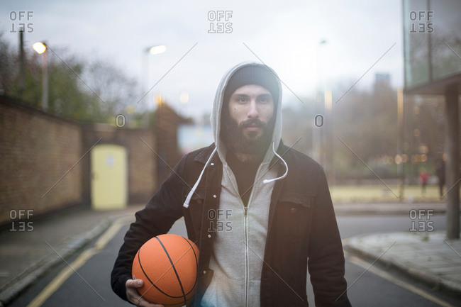 Portrait of mid adult man in street, holding basketball