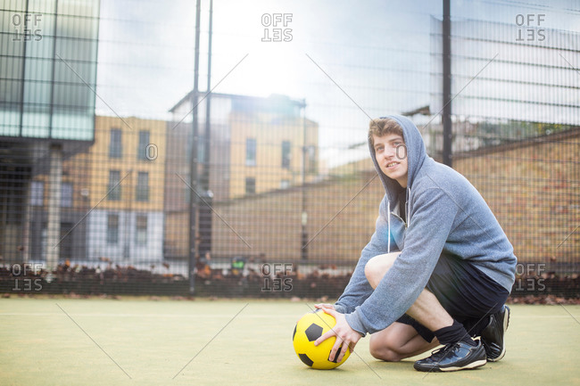 Young man setting soccer on floor, on urban soccer field