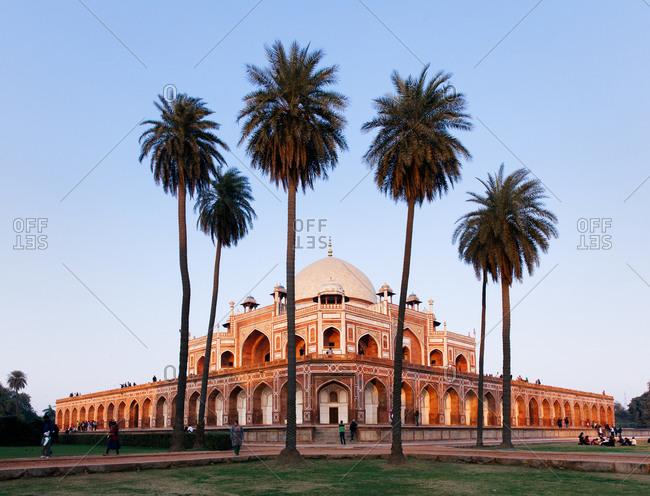 Palm trees and visitors at dusk at Humayun's Tomb in Delhi, India