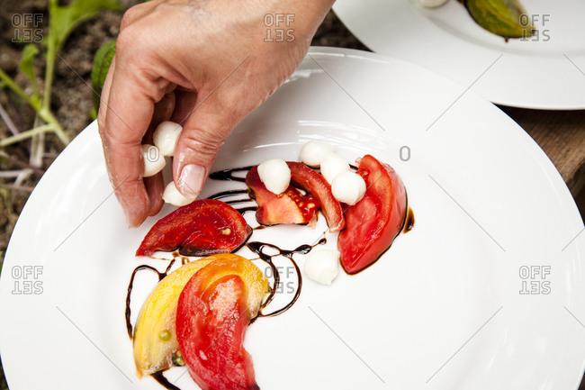 Hand assembling a salad