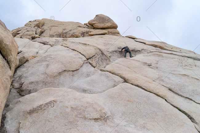 Rock climber scaling cliff at Joshua Tree National Park