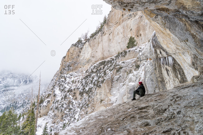 Hiker sitting on cliff overlooking the snowy valley below at Mount Charleston