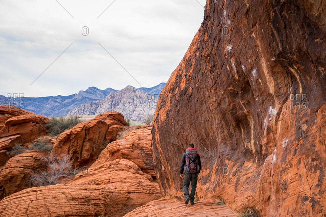 Backpacker hiking on sandstone at Red Rock Canyon, Nevada