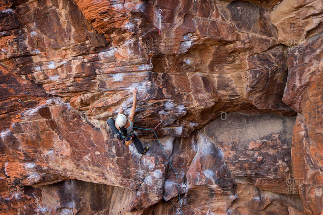Climber scaling a sandstone rock face at Red Rock Canyon, Nevada