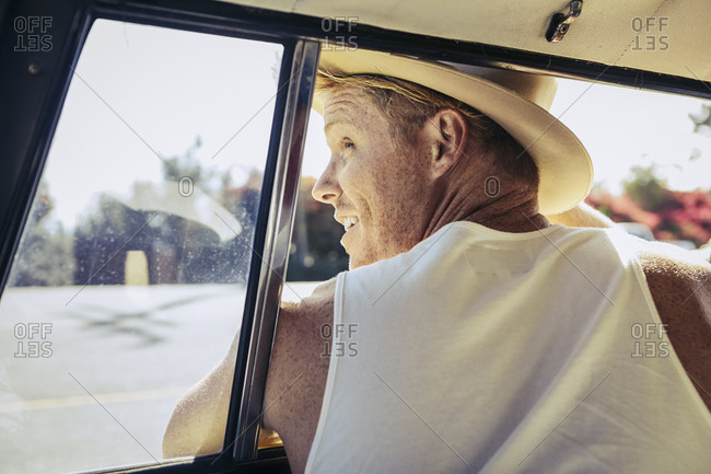 Man leaning out car window to look behind vehicle