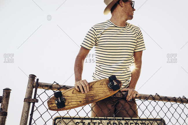 Man in hat and sunglasses climbing over fence with skateboard