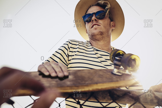 Man in sunglasses and straw hat with a skateboard at fence