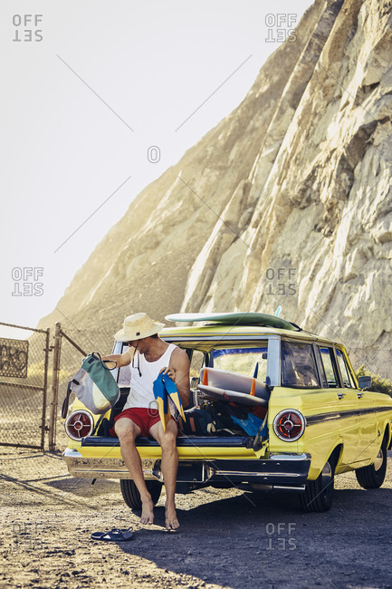 Man sitting in tailgate of vintage station wagon at beach