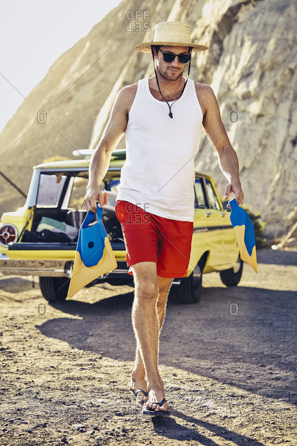 Man walking to beach with pair of swim fins