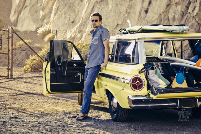 Man leans against vintage station wagon loaded with surfing gear