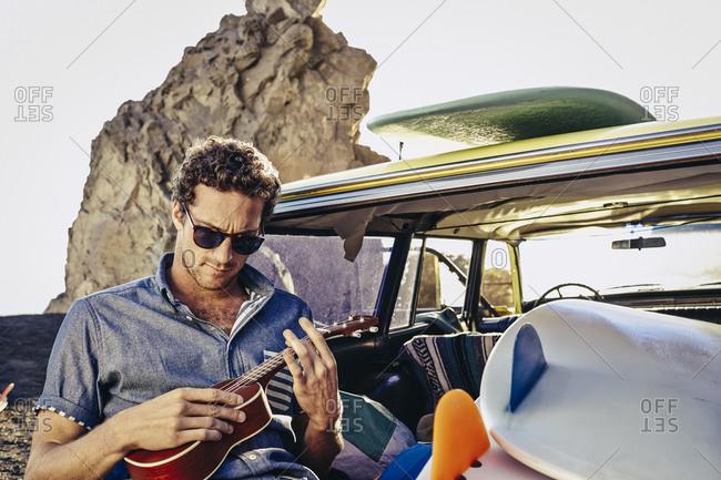 Man plays ukulele in back of vintage surf wagon