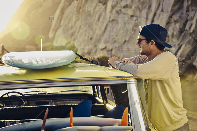 Man tying his surfboard to roof of vintage station wagon