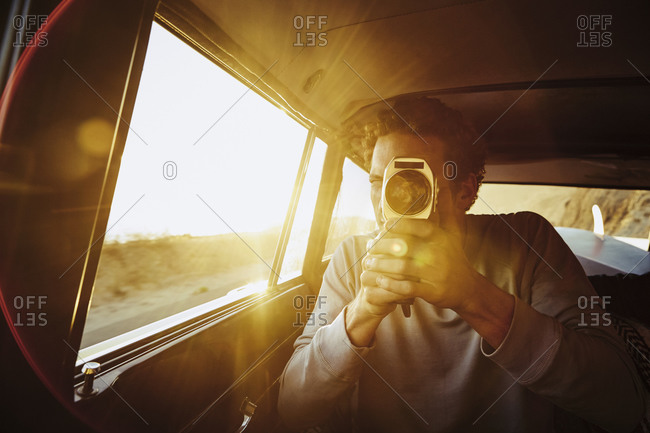 Man with vintage film movie camera in back seat of car