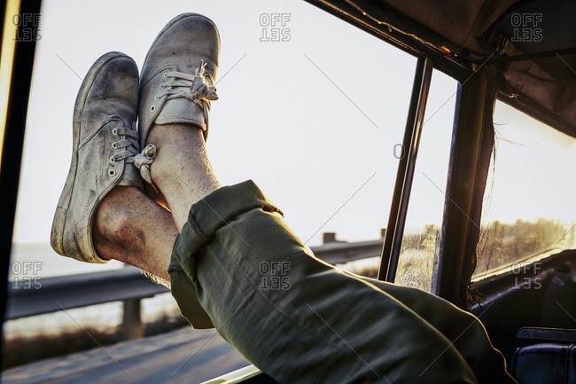 Man rests in back seat of car with dirty shoes hanging out window