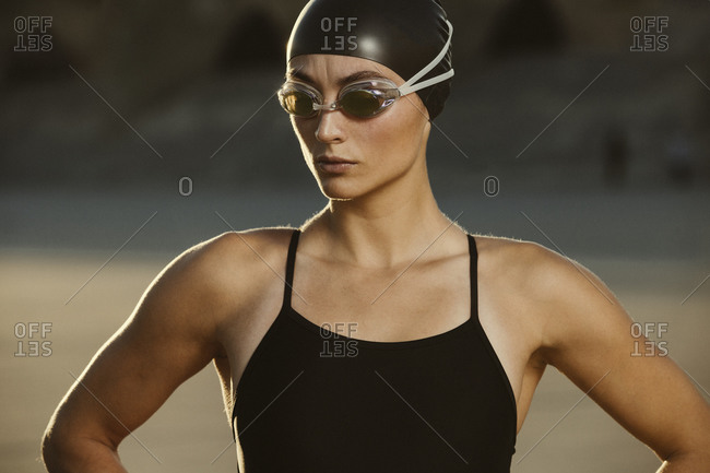 Competitive swimmer standing in golden light on beach
