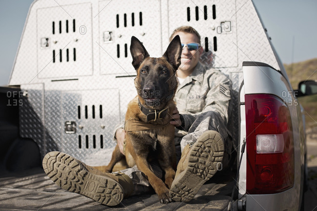 Air Force Staff Sergeant with his trained dog in the bed of a truck